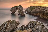 Intense yellow sunrise over a karst rock and rock arch, Asturias, Spain<br /> <br /> Intensiv gelber Sonnenaufgang über einem Karstfelsen und Felsbogen, Asturien, Spanien