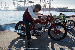 Bryan Thompson of Thompson Cycle starting the 1952 Pre-unit Triumph he built for skateboarding legend Steve Caballero at the Yokohama docks where bikes from invited USA custom builders were unloaded prior to the Mooneyes Yokohama Hot Rod & Custom Show. Yokohama, Japan. December 3, 2016.  Photography ©2016 Michael Lichter.