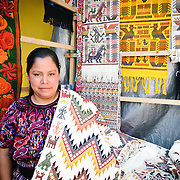 A local woman posing with her woven textiles at the Chichi market. Chichicastenango is an indigenous Maya town in the Guatemalan highlands about 90 miles northwest of Guatemala City and at an elevation of nearly 6,500 feet. It is most famous for its markets on Sundays and Thursdays.