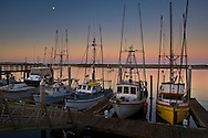 Moon over commercial fishing boats docked in harbor at dawn, Morro Bay, California