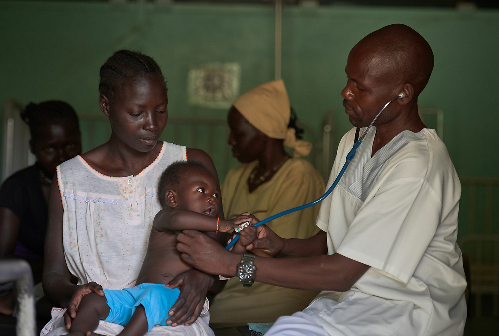 Nurse Elias Shangero Kunnar examines a young patient in the Mother of Mercy Hospital in Gidel, a village in the Nuba Mountains of Sudan. The area is controlled by the Sudan People's Liberation Movement-North, and frequently attacked by the military of Sudan. The Catholic hospital is the only referral hospital in the war-torn area.<br /> <br /> Kunnar is a 2015 graduate of the Catholic Health Training Institute, a school in Wau, South Sudan, sponsored by Solidarity with South Sudan.