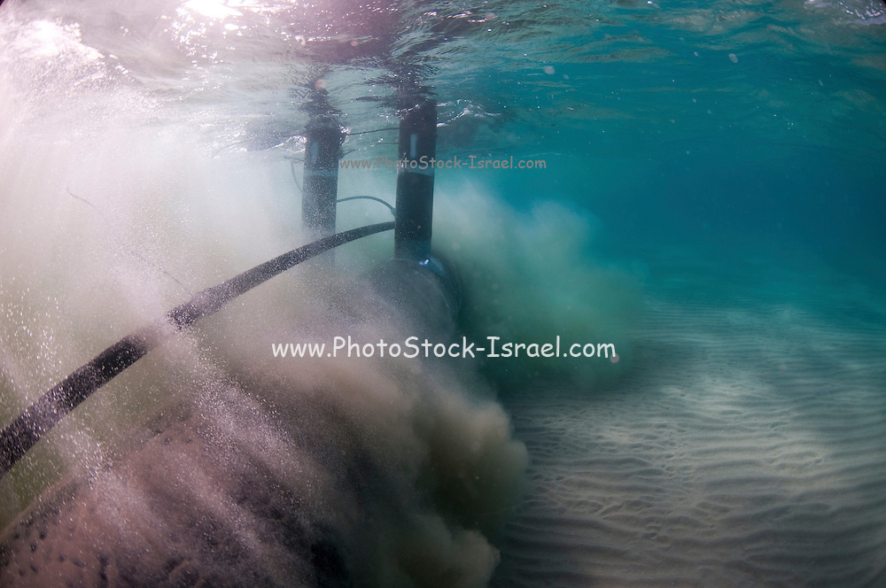Workers laying a brine discharge pipe from a desalination plant on the seabed to a distance of 300 meter from the shore. High pressure water pumped through a perforated pipe surronding the main pipe removes the sand allowing the pipe to settle into the seabed. Brine discharge can have a negative impact on the ocean ecosystem. Photographed in Israel Mediterranean sea