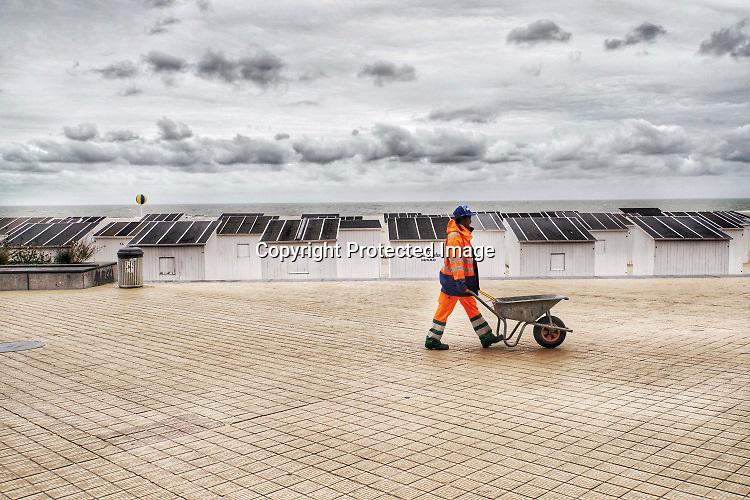 Belgie, Oostende, 6-9-2019Aan het strand langs de Noordzee van deze mondaine badplaats in vlaanderen. Een gemeentewerker van Afrikaanse afkomst loopt met een kruiwagen over de boulevard .Foto: Flip Franssen