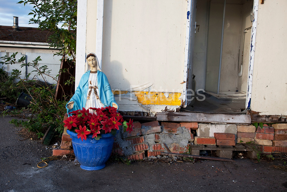 Virgin Mary statue at the entrance to one home. Travellers at Dale Farm site prior to eviction. Riot police and bailiffs were present on 20th October 2011, as the site was cleared of the last protesters chained to barricades. Dale Farm is part of a Romany Gypsy and Irish Traveller site in Crays Hill, Essex, UK<br /> <br /> Dale Farm housed over 1,000 people, the largest Traveller concentration in the UK. The whole of the site is owned by residents and is located within the Green Belt. It is in two parts: in one, residents constructed buildings with planning permission to do so; in the other, residents were refused planning permission due to the green belt policy, and built on the site anyway.
