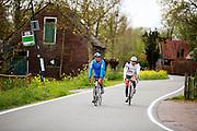In Zegveld rijden twee mannen op een racefiets door het boerenlandschap.<br /> <br /> In Zegveld two cyclists on a road bike cycle at the countryside.