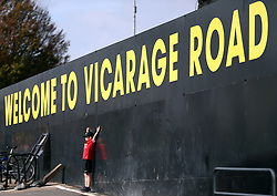 A Manchester United fan poses in front of a Welcome to Vicarage Road sign before the Premier League match at Vicarage Road, Watford