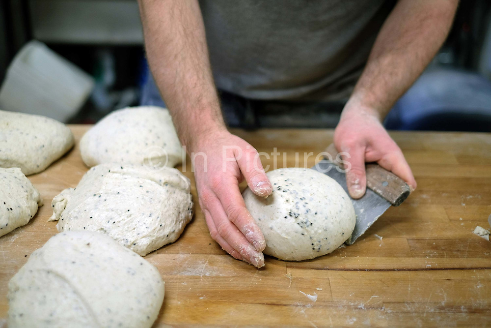 Baker shaping sourdough bread proving at the Haxby Bakehouse, Yorks artisan bakery in Haxby, North Yorkshire, United Kingdom on 10th February 2017. Haxby Bakehouse make bread using traditional methods of slow fermentation. They use low yeasted overnight sponges, natural sourdough levain or a combination of the two. This means the bread they produce is full of flavour without the use of any artificial flour improvers, preservatives or emulsifiers.