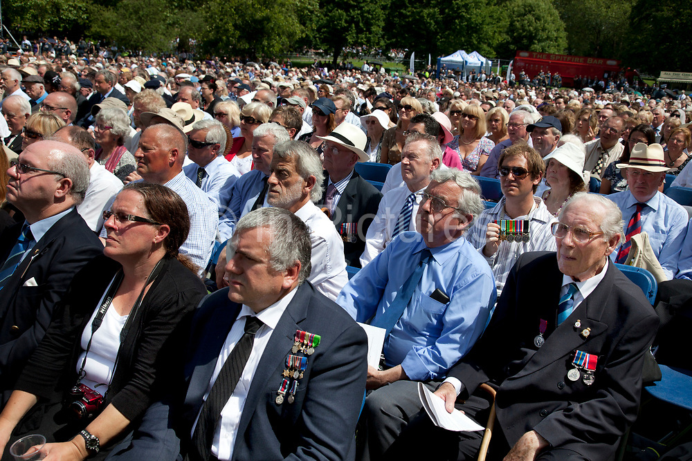Veterans and their families gather in Green park for a service to watch as the memorial to the 55,573 airmen of Bomber Command who died during World War II was unveiled. Some 6000 attended the ceremony. Criticism of large-scale area bombing by the RAF near the end of WWII had stalled plans for a memorial for years. London, England, UK.