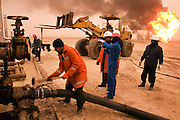 "Firefighters from the Kuwait Oil Company (called KWWK: Kuwait Wild Well Killers) connect hoses to water tanks and pumps near the second oil well fire they were working on in Iraq's Rumaila Oil field. Later in the day they failed to extinguish this fire with water and then tried to stop the flow of gas and oil with drilling mud using what is called a ""stinger,"" a tapered pipe on the end of a long steel boom controlled by a bulldozer. Drilling mud, under high pressure, is pumped through the stinger into the well, stopping the flow of oil and gas. This was also unsuccessful. The Rumaila field is one of Iraq's biggest oil fields with five billion barrels in reserve. Many of the wells are 10,000 feet deep and produce huge volumes of oil and gas under tremendous pressure, which makes capping them very difficult and dangerous. Rumaila is also spelled Rumeilah."