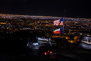 The American and Texas flags wave at half-mast in remembrance of the victims of the Aug. 3 mass shooting, along Scenic Drive in El Paso, Texas, Friday, August 9, 2019. The flags overlook the cityscape of El Paso, Texas in the foreground and Ciudad Juárez, México, in the background, both separated by the southern U.S.-México border.