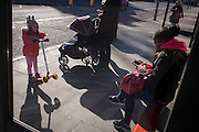 Young girl watches young smoker at a south London bus stop.
