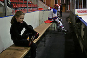 Moscow, Russia, 23/02/2004..Young skaters being trained by chief coach Svetlana Sukolovskaya on the main rink at the TsKA [Central Red Army] club. Veronika Kropotina removes her skates as a men's ice hockey team prepares to begin their practice session at the end of hers...