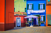 Burano is an island in the Venetian Lagoon, although like Venice itself it could more correctly be called an archipelago of islands linked by bridges. Burano is also known for its small, brightly-painted houses, popular with artists.