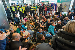 © Licensed to London News Pictures. 10/10/2019. London, UK. Extinction Rebellion protesters block the entrance to London City Airport. Protesters arrived via the Docklands Light Rail and proceeded to conduct a sit-in to block the entrance from the train station to the airport. Photo credit: Peter Manning/LNP