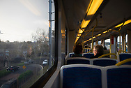 Two people ride a metro train in a neighborhood of Melbourne, Australia, en route to Flinders Street Station in the Central Business District
