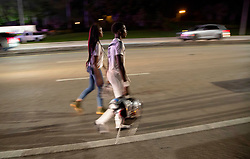 August 18, 2018 - Wellington, Florida, U.S. - A William T. Dwyer High School football player walks down Forest Hill Boulevard after a shooting sent players and fans scattering during the fourth quarter. Two adults were shot Friday night at a football game between Palm Beach Central and William T. Dwyer high schools, authorities said. The gunfire sent players and fans screaming and stampeding in panic during the fourth quarter of the game at Palm Beach Central High School in Wellington, Florida on August 17, 2018. (Credit Image: © Allen Eyestone/The Palm Beach Post via ZUMA Wire)
