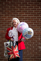 © London News Pictures. 20/07/2013. Royal fan Margaret Tyler holding royal baby balloons for a boy and a girl outside the  Lindo Wing entrance to  St Mary's Hospital in West London where The Duchess of Cambridge is expected to be admitted when she goes into labour. Photo credit: Ben Cawthra/LNP