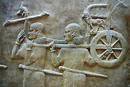 Stone relief sculptured panel of soldiers carrying a chariot . Facade L. Inv AO 19884 from Dur Sharrukin the palace of Assyrian king Sargon II at Khorsabad, 713-706 BC.  Louvre Museum Room 4 , Paris .<br /> <br /> If you prefer to buy from our ALAMY PHOTO LIBRARY  Collection visit : https://www.alamy.com/portfolio/paul-williams-funkystock/ancient-assyria-antiquities.html  Refine search by adding background colour, place, subject, museum etc into the LOWER SEARCH WITHIN GALLERY box to <br /> <br /> Visit our ANCIENT WORLD PHOTO COLLECTIONS for more photos to download or buy as wall art prints https://funkystock.photoshelter.com/gallery-collection/Ancient-World-Art-Antiquities-Historic-Sites-Pictures-Images-of/C00006u26yqSkDOM