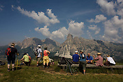 Hikers rest with panoramic views of mountain tops in the Pralongià above San Cassiano-St. Kassian in the Dolomites, south Tyrol, northern Italy. In winter, the Pralongià meadows are the heart of Alta Badia's skiing area. Hiking trails lead across the high alpine pastureland between Corvara and San Cassiano (St. Kassian) with hilly upland meadows with vast mountain pastures and many old hay huts, a pretty group of trees at the edges of the meadows, and the beautiful shapes of the surrounding mountains, which include the Gruppo di Sella (Sellastock) Massif, Sassongher, Monte Cavallo (Heiligkreuzkofel), Cunturines and Lagazuoi.