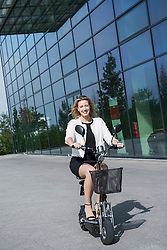 Business woman riding electric powered scooter