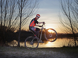 Mature man doing stunts on mountain bike during sunset, Bavaria, Germany