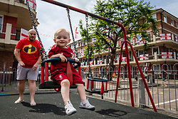 © Licensed to London News Pictures. 15/06/2018. London, UK. Ralph Dowse, 21 months, plays on the swings with his father Chris on the Kirby Estate in Bermondsey, south London, where residents have covered their balconies with hundreds of England flags the World Cup in Russia begins. Photo credit: Rob Pinney/LNP