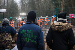 Denham, UK. 7th December, 2020. Anti-HS2 activists in Denham Ford Protection Camp observe contractors and security guards working on the foundations of a bridge across the river Colne in connection with the HS2 high-speed rail link. Activists continue to resist the controversial £106bn rail project from a series of protest camps based along its initial route between London and Birmingham.