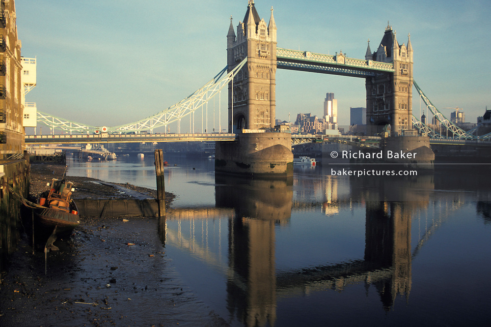 A city landscape showing looking westwards towards Tower Bridge and the river Thames at low-tide with the background of the City of London, the capital's financial district, on 22nd November 1991, in London, England.