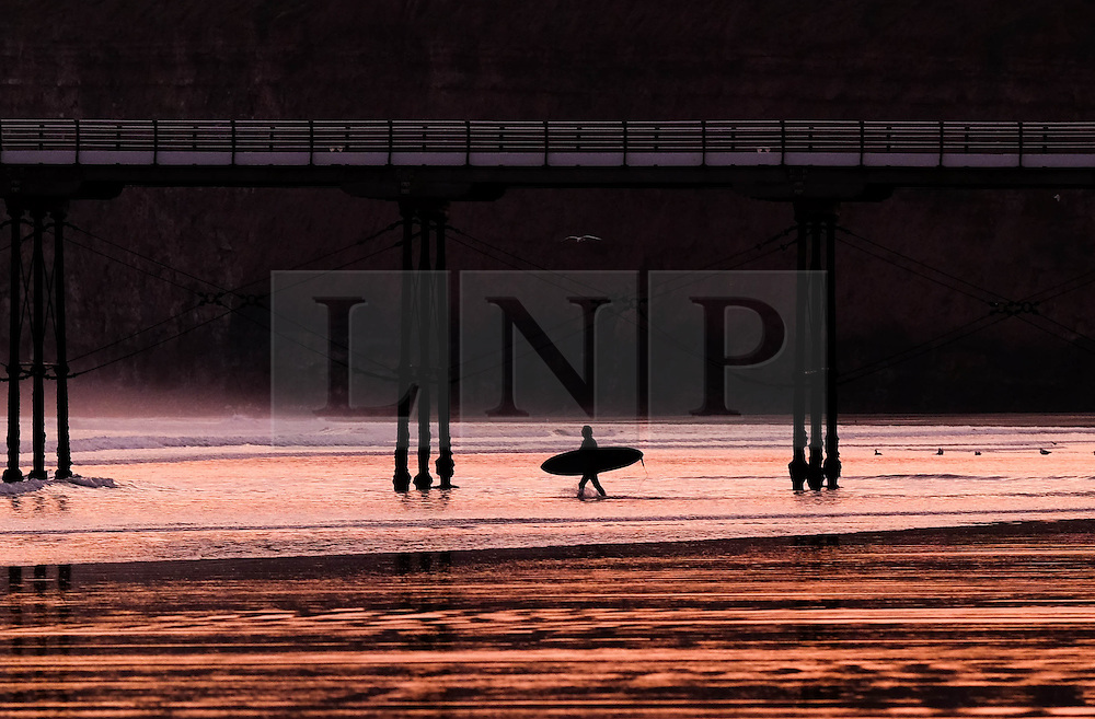 © Licensed to London News Pictures. <br /> 30/10/2016. <br /> Saltburn-by-the-Sea, UK.  <br /> A surfer heads out for a morning surf near the pier as the sun reflects off wet sand at Saltburn-by-the-Sea on the north east coast of England.<br /> Photo credit: Ian Forsyth/LNP