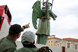 After two months of restoration, the Statue of Archangel Michael, made of copper plate, returned to Piran. The image shows Jure Prezelj and Ales Hocevar of 151st Rotary Wing Squadron before helicopter placing it on top of the church's clock, on October 15, 2018 in Piran, Slovenia. Photo by Matic Klansek Velej / Sportida