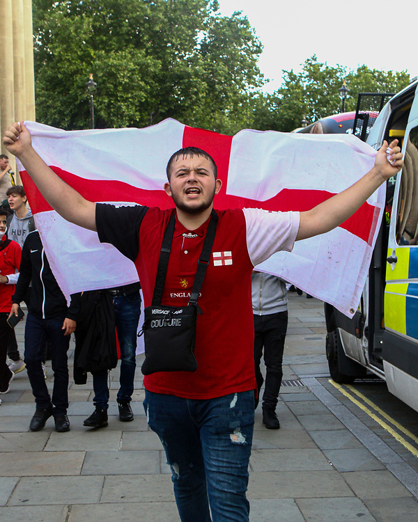 An England supporter walking towards Piccadilly Circus whilst holding the English flag. 03.07.2021. Marcin Riehs/Pathos