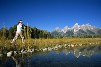 A woman walks along the Snake River with fly fishing gear.  Grand Teton National Park, Jackson Hole, Wyoming.
