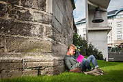 Youngster reading book underneath Klokke Roeland, the symbol of the city Ghent, Belgium, 08.10.2015