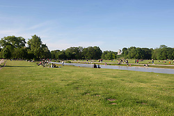 May 23, 2019 - Munich, Bavaria, Germany - People lying on the grass next to the Eisbach river with a view on the Monopteros. On  May 23, 2019 the people passed the afternoon and evening in the English Garden. (Credit Image: © Alexander Pohl/NurPhoto via ZUMA Press)