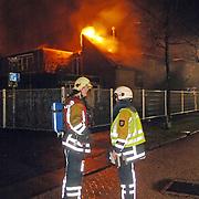 NLD/Huizen/20060310 - Uitslaande brand leegstaand pand de Boketorren Hermelijn Huizen, brandweer haalt met pompen water uit de singels