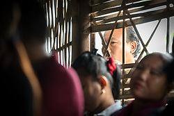 14 September 2018, Damak, Nepal:  Supported by the Lutheran World Federation, the Beldangi refugee camp in the Jhapa district of Nepal hosts more than 5,000 Bhutanese refugees. Here, a man looks through the window as LWF general secretary Rev. Dr Martin Junge visits the camp.