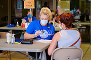 """26 JUNE 2021 - DES MOINES, IOWA: A medical volunteer triages a patient during the RAM clinic in Des Moines, Saturday, June 26. Remote Area Medical (RAM) is a nonprofit provider of free pop-up clinics. Their mission is to prevent pain and alleviate suffering by providing free, quality healthcare to those in need. They do this by delivering free dental, vision, and medical services to underserved and uninsured individuals. The clinic in Des Moines was RAM's first clinic in Iowa. RAM was hoping to see 250 people during the two day """"pop up"""" clinic.       PHOTO BY JACK KURTZ"""