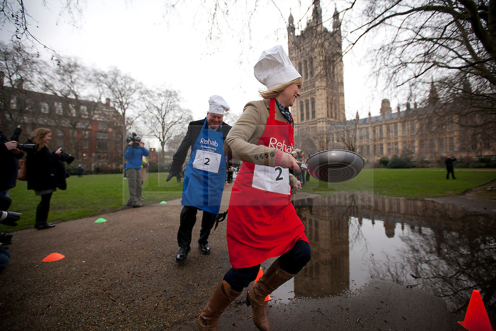 © Licensed to London News Pictures. 12/02/2013. London, UK. British politicians and members of the media toss pancakes as they take part in the annual Rehab Parliamentary Pancake Race in Westminster, London today (12/02/2013).The race involving MPs from the House of Commons, Lords from the House of Lords and members of the Parliamentary Press Gallery, is aimed at raising awareness for the Rehab; a charity that works to support people with disabilities, takes place every year in Victoria Tower Gardens next to Parliament and was won this year by the House of Commons team. Photo credit: Matt Cetti-Roberts/LNP