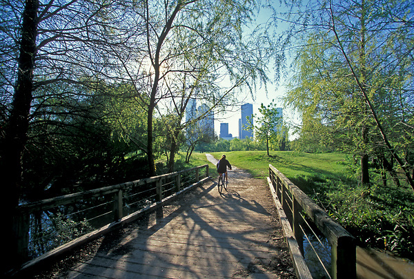 Stock photo of a woman riding her bicycle across a wooden bridge in Buffalo Bayou Park
