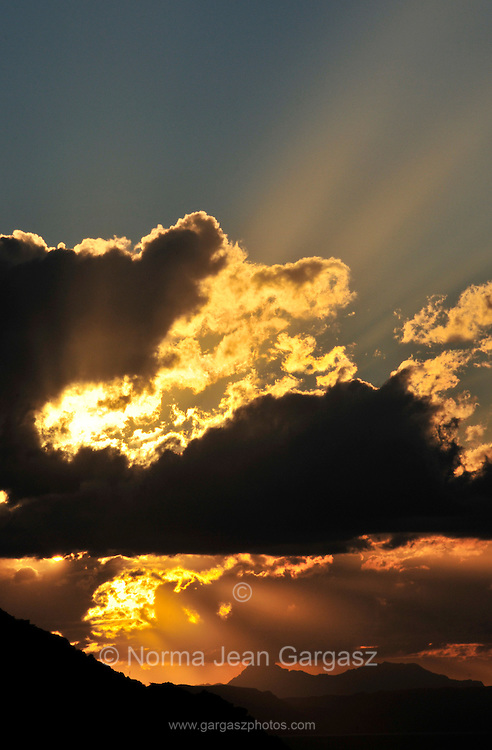 The setting sun illuminates Baboquivari Peak, (in distance on left) , the most sacred place to the Tohono O'odham people. Located 50 miles southwest of Tucson, Arizona, USA, in the Baboquivari Mountains and Baboquivari Peak Wilderness it is the center of the Tohono O'odham cosmology and the home of the creator, I'itoi.