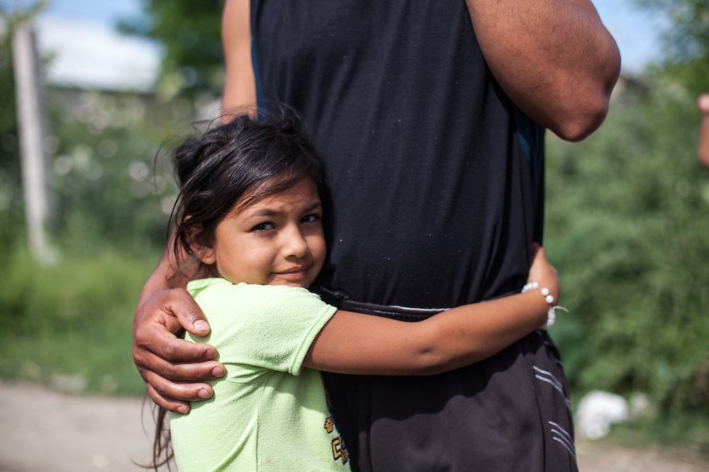 Portrait of a girl holding her father in the Roma area of Frumusani.