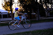 11 year old girl riding bicycle, backlit by setting sun. Perth, Western Australia