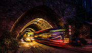 Streaks of lights as trams from opposite directions pass at the tunnel entrance below Bratislava castle