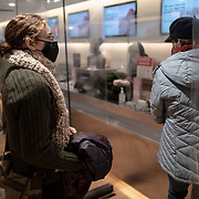 Shoppers stand in a socially distanced clothing store checkout line during the Coronavirus (Covid-19) outbreak in Manhattan,New York on Sunday, December 6, 2020. (Alex Menendez via AP)