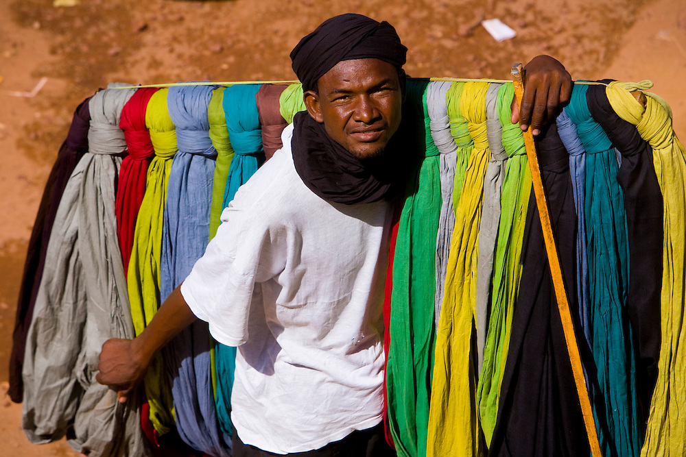 Street vendor selling colored fabrics. At the confluence of the Niger and the Bani rivers, between Timbuktu and Segou, Mopti is the second largest city in Mali, and the hub for commerce and tourism in this west-african landlocked country.