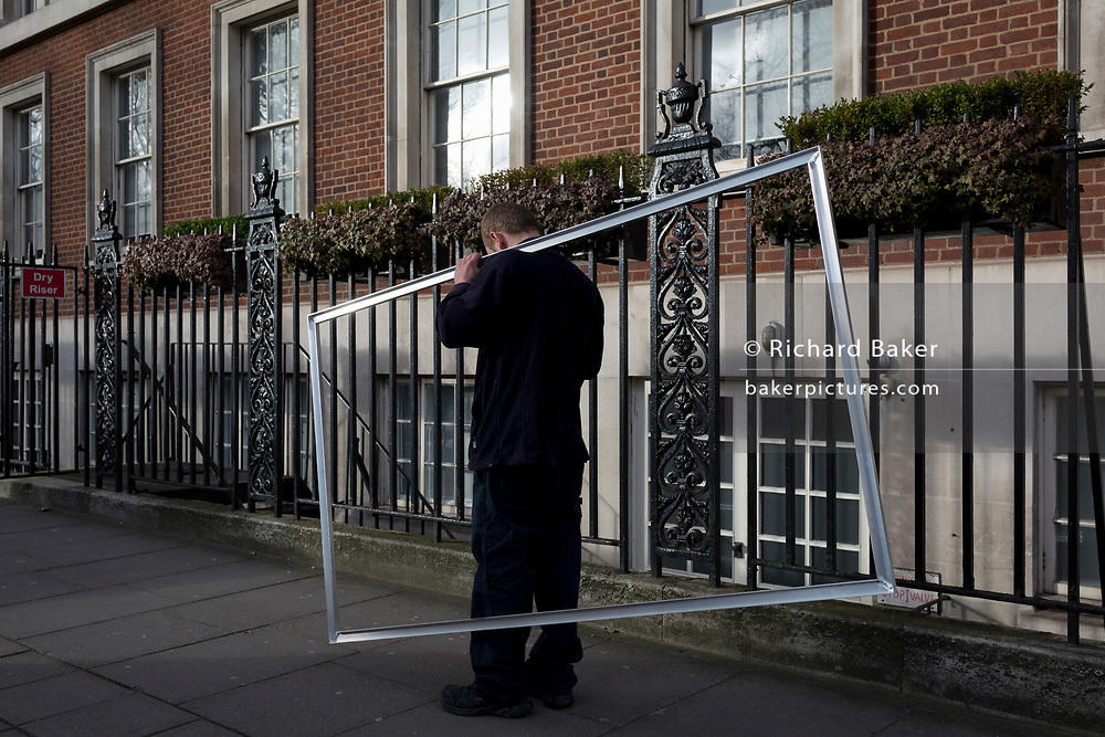 A workman delivers a rectangular frame, on 17th January 2018 in Grosvenor Square, Westminster, London, England.