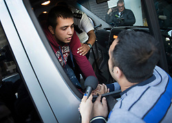 © Licensed to London News Pictures. 17/10/2016. Croydon, UK. 16 year old Afghanistani refugee 'Haris' (L) is held back by an immigration official as he talks to his uncle Jan Ghazi (R) from a bus, as the first children from the Calais jungle refugee camp leave the Home Office immigration centre in Croydon. British authorities are bringing over about 100 children this week to be reunited with their relatives. The French government have announced that they will be dismantling the camp this month. credit: Peter Macdiarmid/LNP