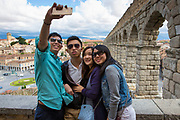 Young Chinese tourists taking selfie photographs with iPhone smartphone at famous Roman aqueduct, Segovia, Spain