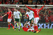 Joe Allen of Wales hits the floor dazed after taking a knock from James McClean (11) and David Meyler (18) of Republic of Ireland, the incident leads to Allen leaving injured. Wales v Rep of Ireland , FIFA World Cup qualifier , European group D match at the Cardiff city Stadium in Cardiff , South Wales on Monday 9th October 2017. pic by
