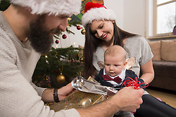 Father unwrapping gift for his son